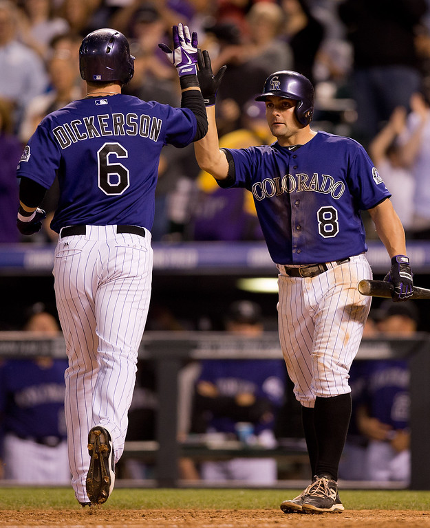. Corey Dickerson #6 of the Colorado Rockies is congratulated at home plate after his solo home run by Michael McKenry #8 during the seventh inning against the Atlanta Braves at Coors Field on June 9, 2014 in Denver, Colorado.  (Photo by Justin Edmonds/Getty Images)