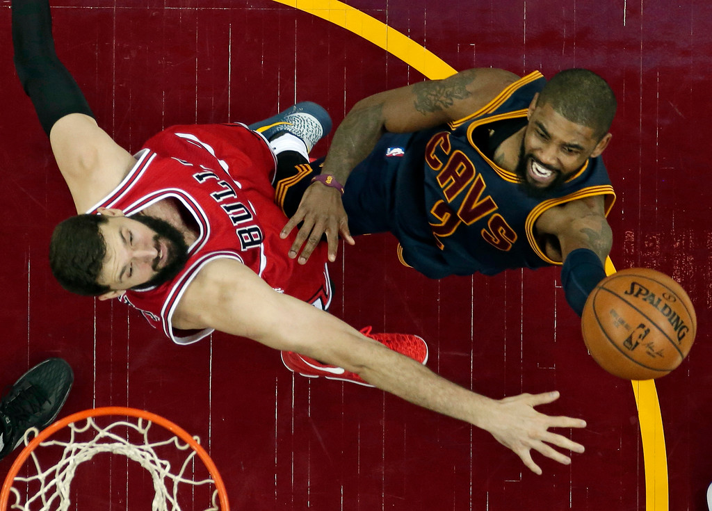 . Cleveland Cavaliers\' Kyrie Irving, right, shoots against Chicago Bulls\' Nikola Mirotic during the second half of an NBA basketball game, Saturday, Feb. 25, 2017, in Cleveland. The Bulls won 117-99. (AP Photo/Tony Dejak)