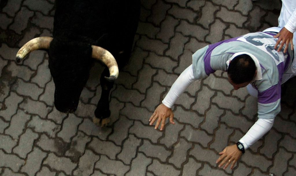 . A runner falls next to a Torrestrella fighting bull at the entrance to the bull ring during the fifth running of the bulls of the San Fermin festival in Pamplona July 11, 2013. No serious injuries were reported in a run that lasted two minutes and forty five seconds, according to local media. REUTERS/Joseba Etxaburu