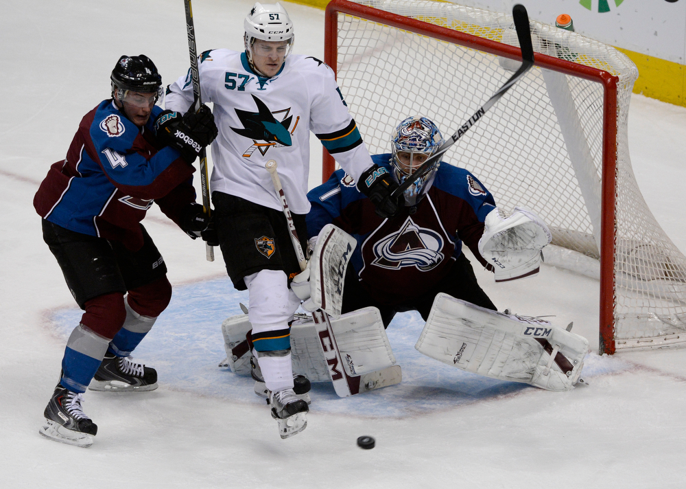 . Colorado Avalanche goalie, Semyon Varlamov, keeps his eyes on the puck as teammate, Tyson Barrie, left, battles San Jose Sharks center, Tommy Wingels in front of the net during the second period of play at the Pepsi Center Saturday afternoon, March 29, 2014. The Av\'s won 3-2 securing a playoff spot with the win. (Photo By Andy Cross / The Denver Post)