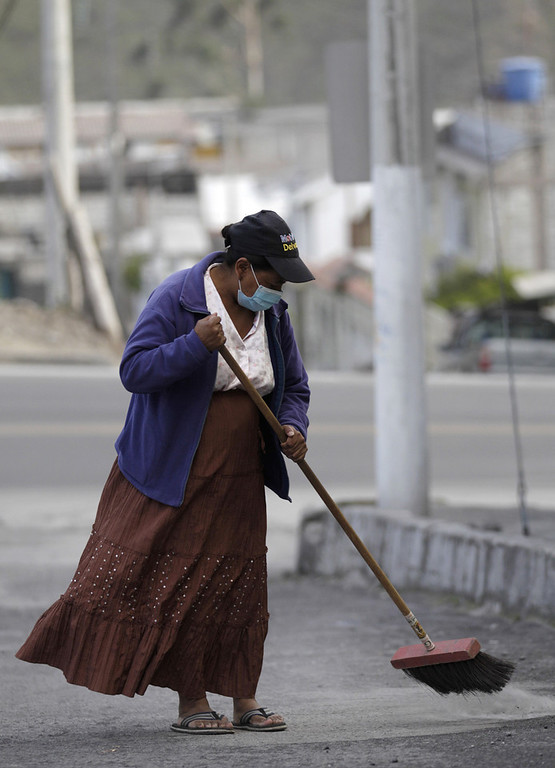 . A woman sweeps up volcanic ash spewed from the nearby Tungurahua volcano in, Banos, Ecuador, Monday, Dec. 17, 2012. The country\'s National Geophysics Institute says that a constant plume of gas and ash is rising about half a mile (1 kilometer) above the crater, with ash falling on nearby communities.  (AP Photo/Dolores Ochoa)