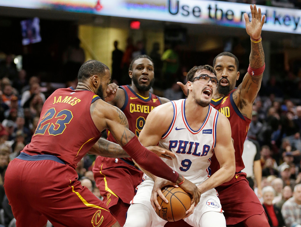 . Philadelphia 76ers\' Dario Saric, center, from Croatia, tries to get past Cleveland Cavaliers\' LeBron James, left, Jae Crowder and JR Smith, right, during the first half of an NBA basketball game, Saturday, Dec. 9, 2017, in Cleveland. (AP Photo/Tony Dejak)