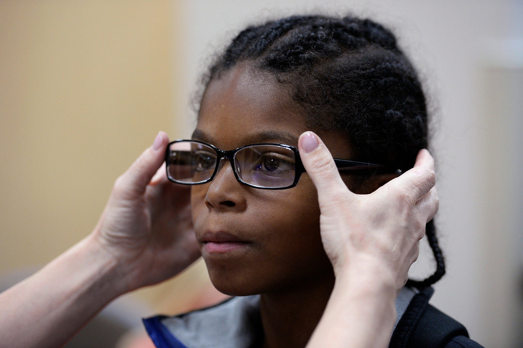 . Jaqlike Riley, 10, gets fitted with prescription glasses by Jina Schaff, O.D. at the event. (Photo by John Leyba/The Denver Post)