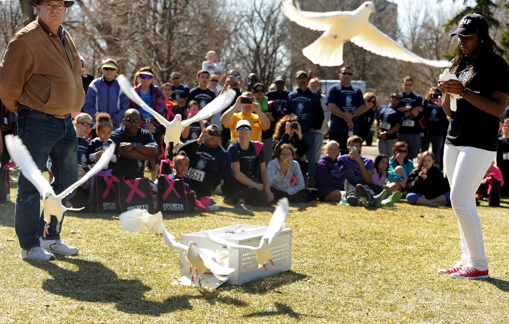. Amyre Hollis, right, the 14 year old daughter of Celena, gets ready to release 1 of the 22 doves during the gathering after the race as the other doves fly by. Tom Loux, the dove keeper, is at left.  Family, colleagues, and friends of slain Denver Police Officer Celena Hollis turned out April 7, 2013 for a 5k run and walk to raise money for a scholarship fun and a memorial bench in City Park in Denver, CO.  Over 300 runners and walkers participated in the race that started at 9:00 am.  The race looped around City Park.  After the race, a gathering was held to remember Hollis and 22 white doves were released in her memory.  (Photo By Helen H. Richardson/ The Denver Post)