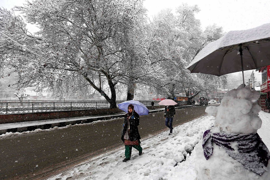 . A Kashmiri woman walks with umbrella on a snow-covered road in Srinagar, India, Tuesday, Dec. 31, 2013. Snowfall in the Indian portion of Kashmir has disrupted power supply, air traffic and road traffic between Srinagar and Jammu, the summer and winter capitals of India\'s Jammu-Kashmir state, according to news reports. (AP Photo/Dar Yasin)