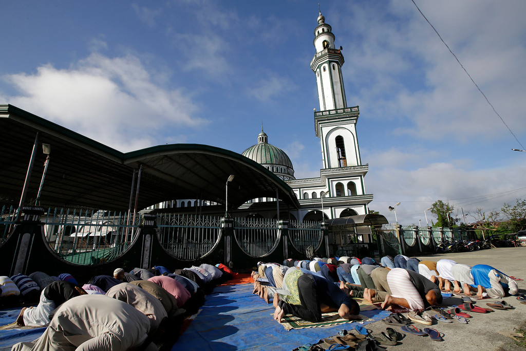 . Survivors offer Eid al-Fitr prayers outside the Saduc Grand Mosque, the biggest mosque that reopened near the former battle area between troops and Islamic extremists, to mark the end of the holy fasting month of Ramadan in Marawi city, southern Philippines,Friday, June 15, 2018. Thousands of displaced residents celebrated Eid al-Fitr inside emergency shelters and the threat of Islamic extremists and unexploded bombs lingers in the rubble after a disastrous five-month siege by Islamic State group-aligned fighters that began more than a year ago. (AP Photo/Aaron Favila)