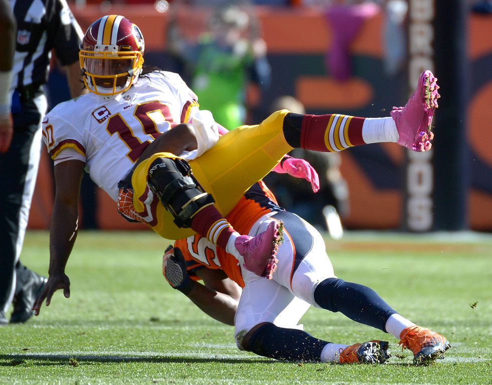 . Washington Redskins quarterback Robert Griffin III (10) is hit as he releases the ball by Denver Broncos outside linebacker Danny Trevathan (59) during the first half.   (Photo by Tim Rasmussen/The Denver Post)