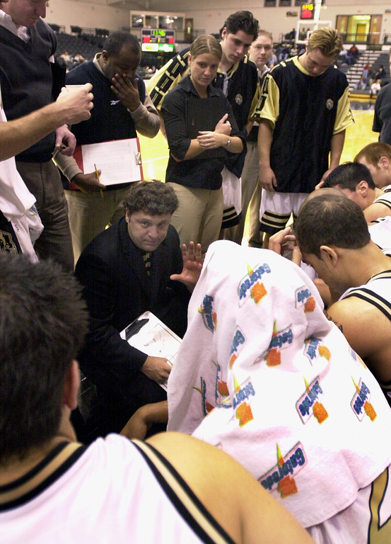 . Oakland University mens basketball head coach Greg Kampe, bottom left, gives instructions to his team during a timeout as they played the Premier All-Stars AAU, during first half action, Saturday, November 10, 2001, at the O\'rena in Rochester Hills, Mich.
