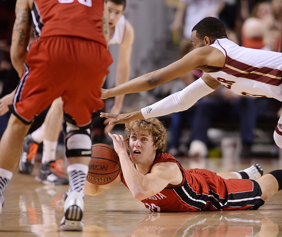 . South Dakota guard Brandon Bos goes to the court, scrambling for a loose ball in the second against Denver in an NCAA college basketball game Saturday, Feb. 8, 2014, in Denver. Denver won 75-67. (AP Photo/The Denver Post, Karl Gehring)
