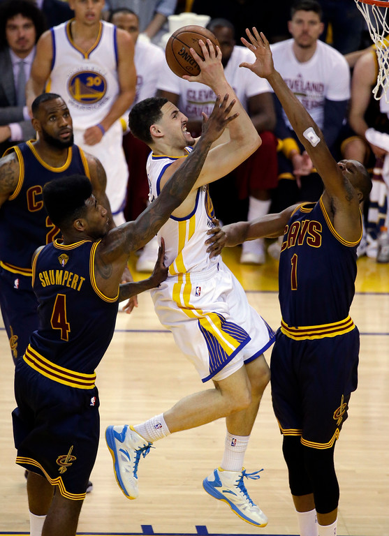 . Golden State Warriors guard Klay Thompson, center, shoots between Cleveland Cavaliers guard Iman Shumpert (4) and forward James Jones during the second half of Game 5 of basketball\'s NBA Finals in Oakland, Calif., Sunday, June 14, 2015. (AP Photo/Eric Risberg)