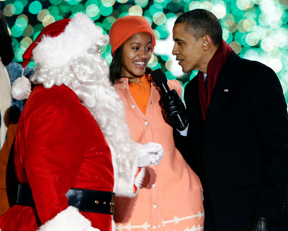 . President Barack Obama, right, and daughter Malia Obama, sing as Santa Claus arrives during the 90th annual National Christmas Tree Lighting ceremony on the Ellipse south of the White House, Thursday, Dec. 6, 2012, in Washington. (AP Photo/Alex Brandon)