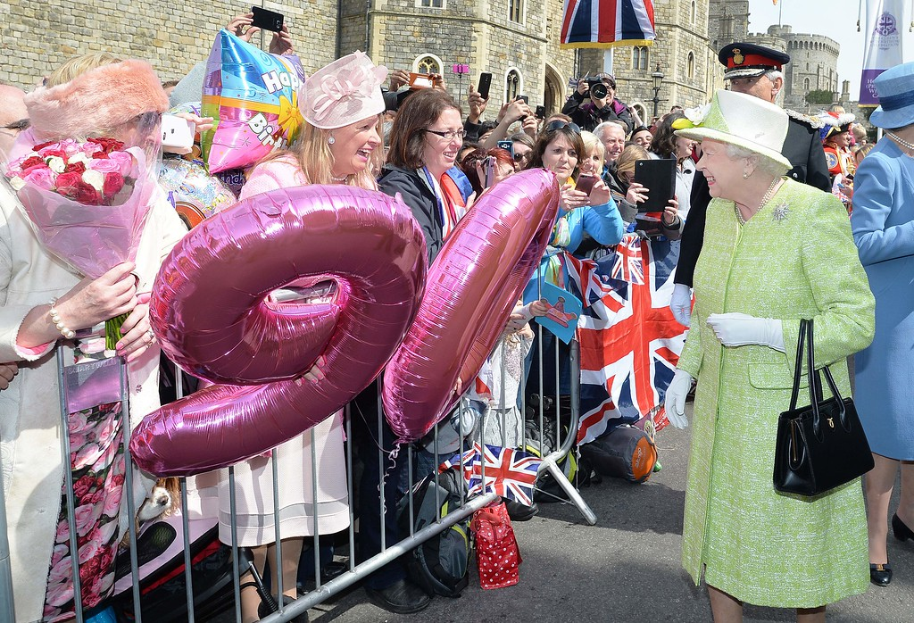 . Britain\'s Queen Elizabeth II greets well-wishers during a \'walkabout\' on her 90th birthday in Windsor, west of London, on April 21, 2016. Britain celebrates Queen Elizabeth II\'s 90th birthday on Thursday, with her eldest son Prince Charles paying tribute in a special radio broadcast and Prime Minister David Cameron leading a parliamentary homage. / AFP PHOTO / POOL / John STILLWELL/AFP/Getty Images