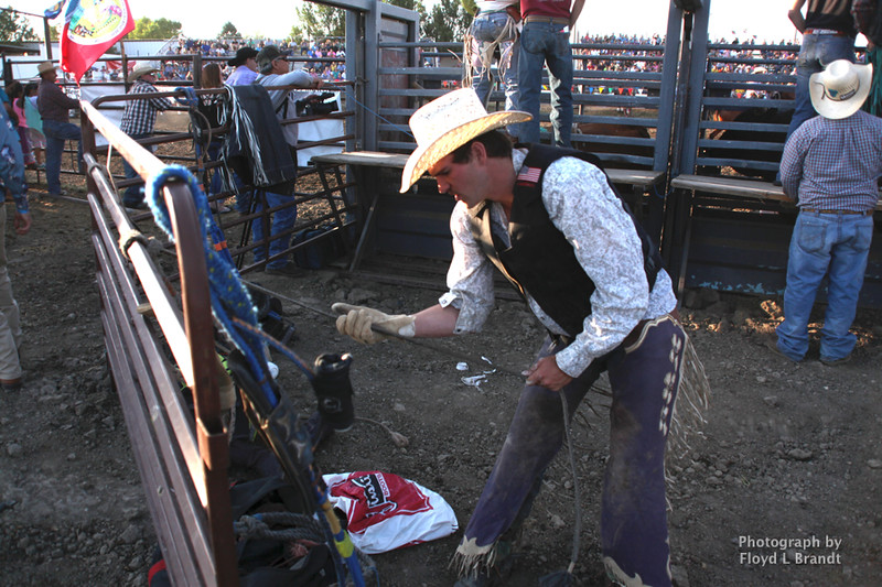 Havre Daily News / Floyd Brandt  Bull rider Connor Murnion from Jordan Montana prepares his rigging for riding Bail Jumper at the Great Northern Fair in Hill County Friday