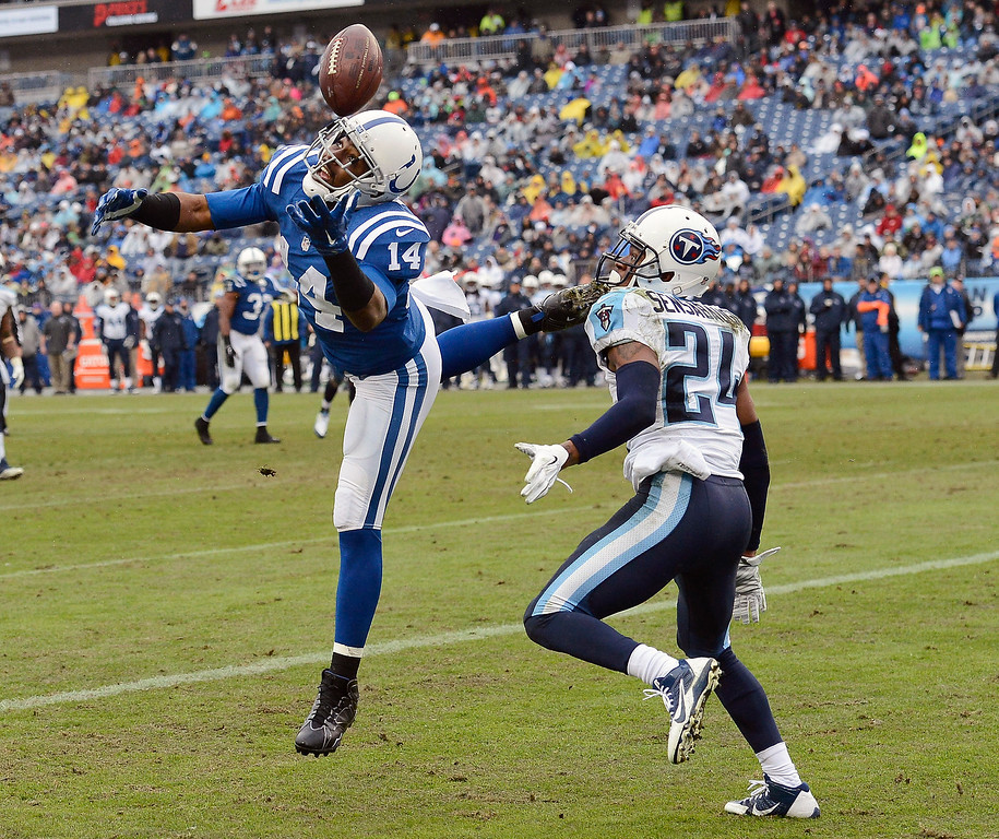 . Indianapolis Colts wide receiver Hakeem Nicks (14) tries unsuccessfully to grab a pass as he is defended by Tennessee Titans cornerback Coty Sensabaugh (24) in the second half of an NFL football game Sunday, Dec. 28, 2014, in Nashville, Tenn. (AP Photo/Mark Zaleski)
