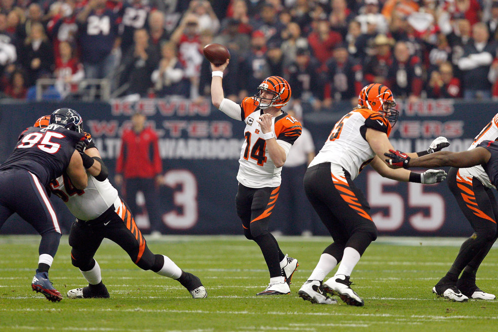 Description of . Andy Dalton #14 of the Cincinnati Bengals throws a pass in the first half against the Houston Texans during their AFC Wild Card Playoff Game at Reliant Stadium on January 5, 2013 in Houston, Texas.  (Photo by Bob Levey/Getty Images)