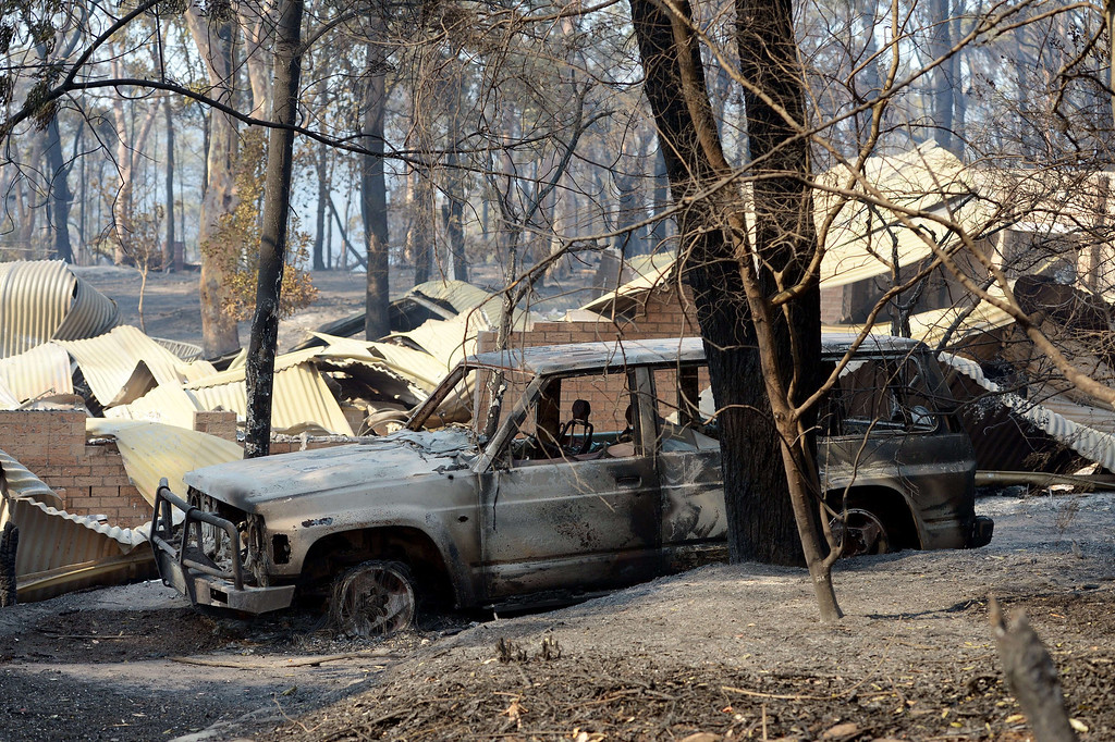 . A burnt out car (C) sits at the front of a house destroyed by bush fires in Winmalee in Sydney\'s Blue Mountains on October 18, 2013. AFP PHOTO / Greg WOOD/AFP/Getty Images