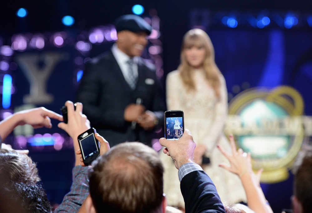 Description of . Music fans take cell phone photos of LL Cool J and Taylor Swift onstage at The GRAMMY Nominations Concert Live!! held at Bridgestone Arena on December 5, 2012 in Nashville, Tennessee.  (Photo by Michael Kovac/Getty Images)