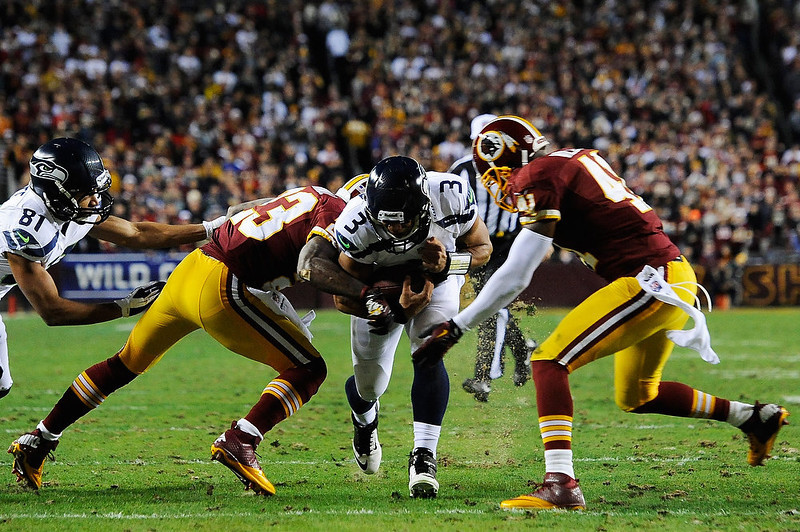 . Russell Wilson #3 of the Seattle Seahawks is tackled by  Madieu Williams #41 and  DeAngelo Hall #23 of the Washington Redskins during the NFC Wild Card Playoff Game at FedExField on January 6, 2013 in Landover, Maryland.  (Photo by Patrick McDermott/Getty Images)