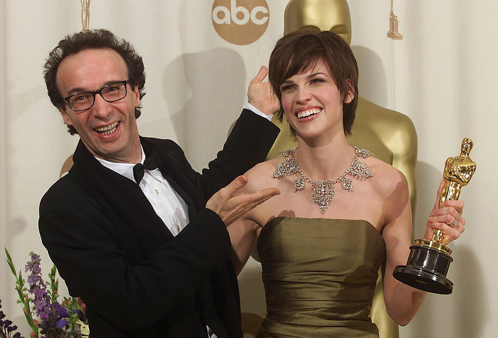 Description of . Italian actor Roberto Benigni (L) and Hilary Swank joke at the Academy Awards presentation 26 March 2000. Swank won for Best Actress for her role in