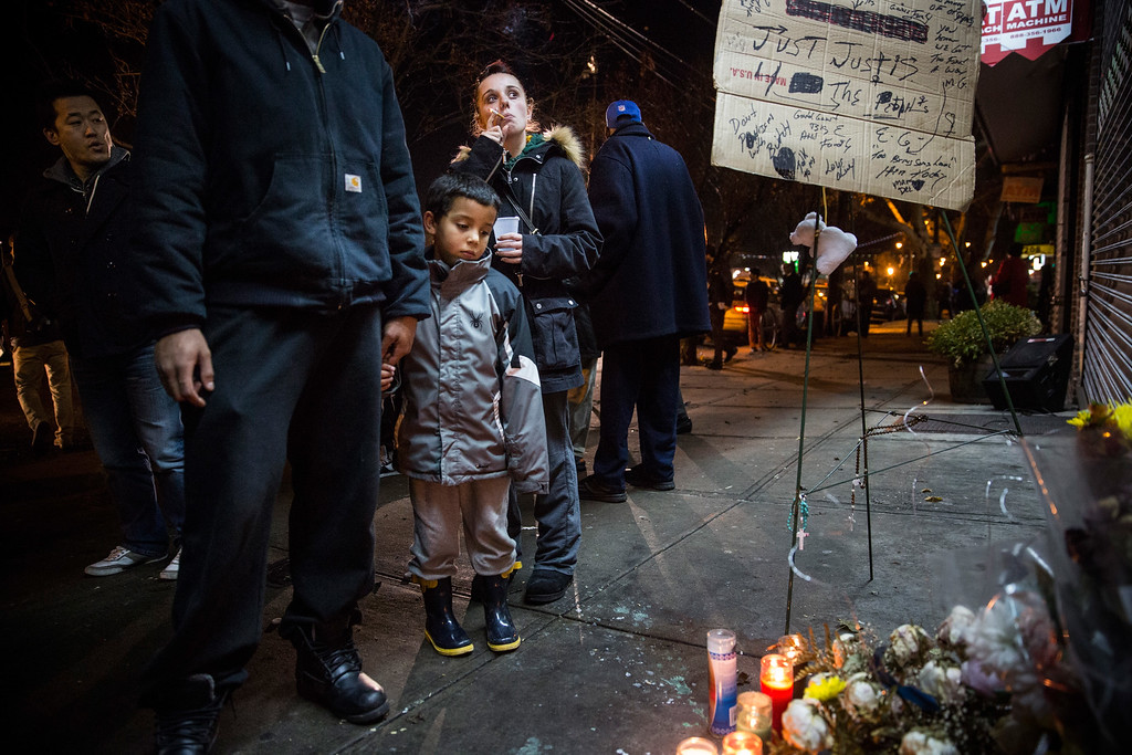 . NEW YORK, NY - DECEMBER 03:  Robert Corulla and Crystal Demaio hold their son, Edward Corulla, 6, during a vigil for Eric Garner, the man killed by a police officer in July using a chokehold, outside the beauty salon where the confrontation took place on December 3, 2014 in the Staten Island borough of New York City. A grand jury declined to indict New York City Police Officer Daniel Pantaleo in Garner\'s death.  (Photo by Andrew Burton/Getty Images)