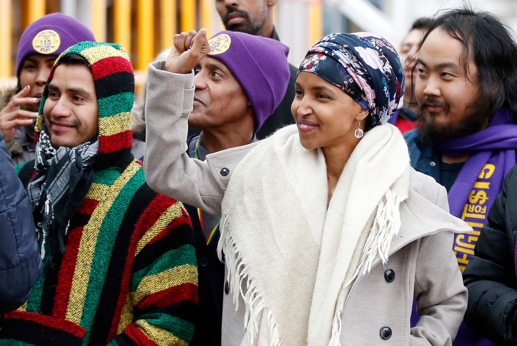 . Ilhan Omar, right, the first Somali-American elected to a state legislature, raises a fist during a rally including airport workers Tuesday, Nov. 29, 2016, at the Minneapolis-St. Paul International Airport in Minneapolis, in support of $15 minimum wages. Omar was elected to the Minnesota House. (AP Photo/Jim Mone)