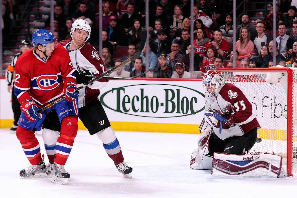 . Jean-Sebastien Giguere #35 of the Colorado Avalanche stops the puck in front of teammate Nick Holden #2 and Travis Moen #32 of the Montreal Canadiens during the NHL game at the Bell Centre on March 18, 2014 in Montreal, Quebec, Canada.  (Photo by Richard Wolowicz/Getty Images)