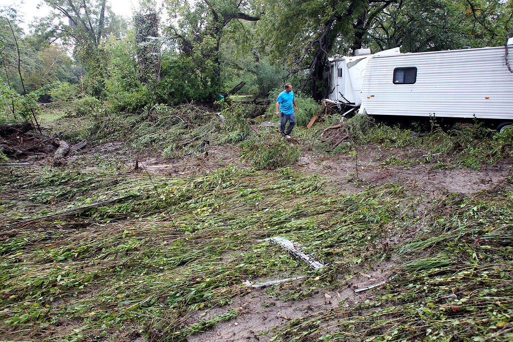 . Ken Posey inspects an RV trailer nestled downstream from the River Ranch RV Resort after the Guadalupe and Comal Rivers flowed over their banks in New Braunfels, Texas, on Thursday, Oct. 31, 2013.  The National Weather Service said more than a foot of rain fell in Central Texas, including up to 14 inches in Wimberley, since rainstorms began Wednesday. (AP Photo/San Antonio Express-News, Tom Reel)