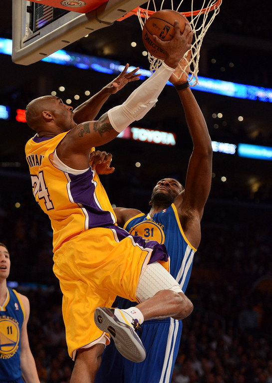. The Lakers\' Kobe Bryant #24 shoots as the Warriors\' Festus Ezeli #31 defends during their game at the Staples Center in Los Angeles Friday, April 12, 2013. (Hans Gutknecht/Staff Photographer)