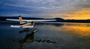 Cessna seaplane taxiing to an evening takeoff