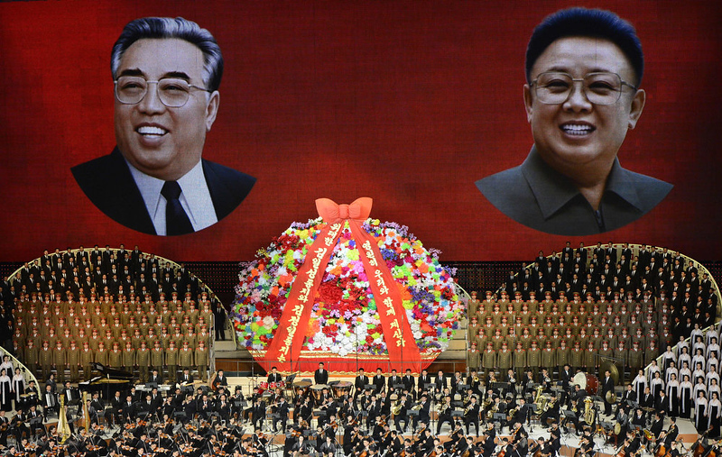 . North Korean performers sing in front of portraits of founding president Kim Il-Sung (L) and his son Kim Jong-Il during celebrations to mark the 100th birth anniversary of the country\'s founding leader Kim Il-Sung, in Pyongyang on April 16, 2012.  The commemorations came just three days after a satellite launch timed to mark the centenary fizzled out embarrassingly when the rocket apparently exploded within minutes of blastoff and plunged into the sea.   AFP PHOTO / PEDRO UGARTE
