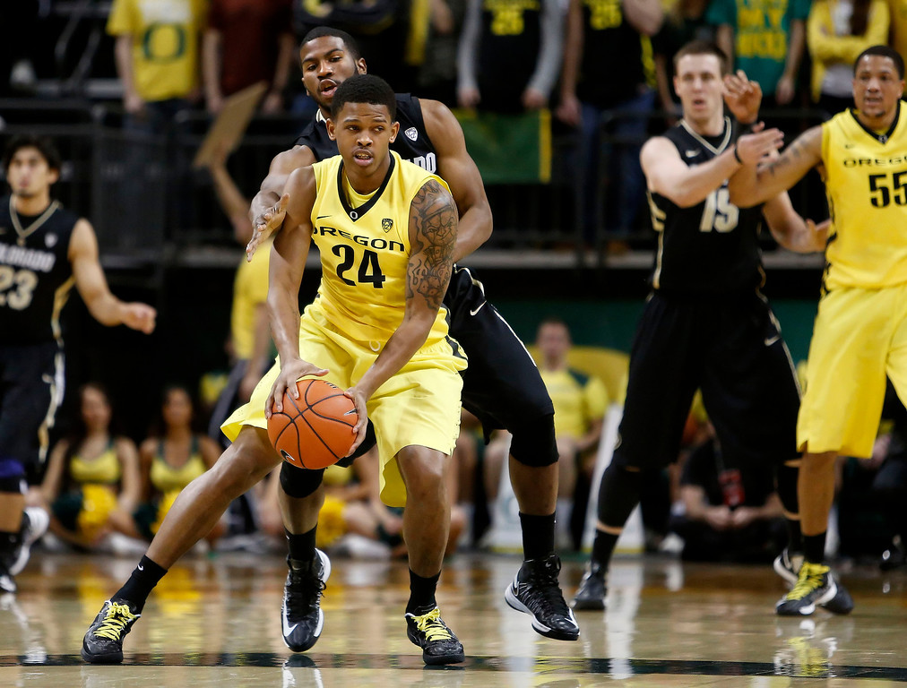 . Colorado\'s Jeremy Adams defends Oregon\'s Willie Moore (24) during the first half of  an NCAA college basketball game at Matthew Knight Arena in Eugene, Ore. Thursday, Feb. 7, 2013. (AP Photo/Brian Davies)