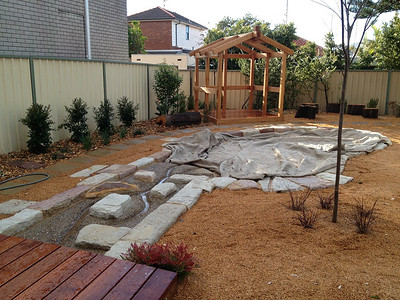 stream bed with sandstone block edging and sandpit and open plan timber cubby and log round seating