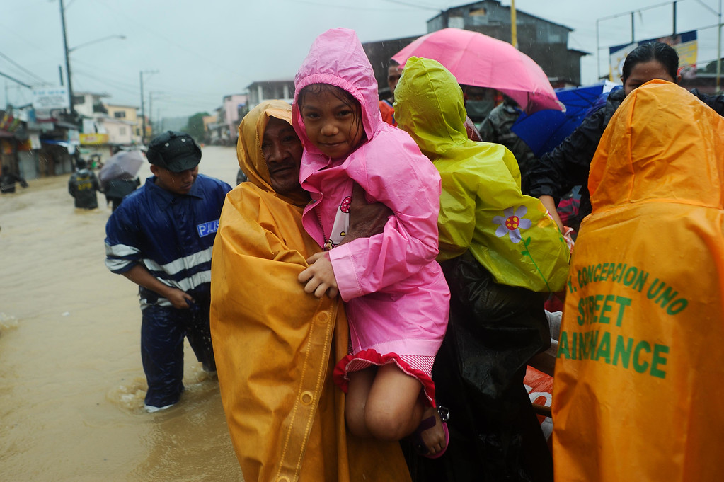 . Residents are rescued by police and rescue volunteers after continued monsoon rains triggered by tropical storm Fung-Wong have inundated parts of Marikina on September 19, 2014 in Manila, Philippines.  (Photo by Dondi Tawatao/Getty Images)