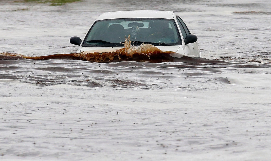 . A driver tries to navigate a severely flooded street as heavy rains pour down Monday, Sept. 8, 2014, in Phoenix. Storms that flooded several Phoenix-area freeways and numerous local streets during the Monday morning commute set an all-time record for rainfall in Phoenix in a single day. (AP Photo/Ross D. Franklin)