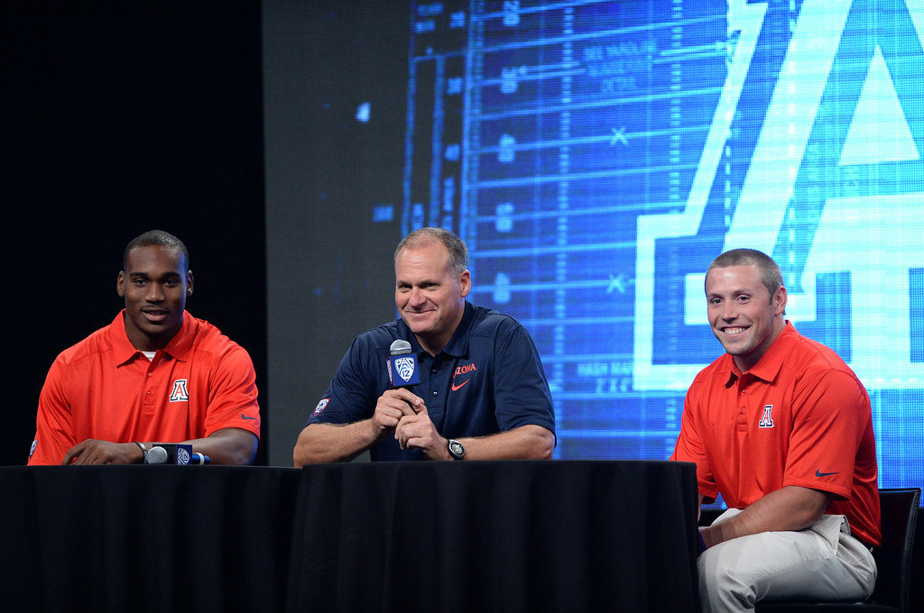 . Arizona Coach Rich Rodriguez, center, with players Terrence Miller(WR), left, and Jake Fischer, (LB) right. Pac12 media Day at Sony Studios.  Photo by Brad Graverson 7-26-13