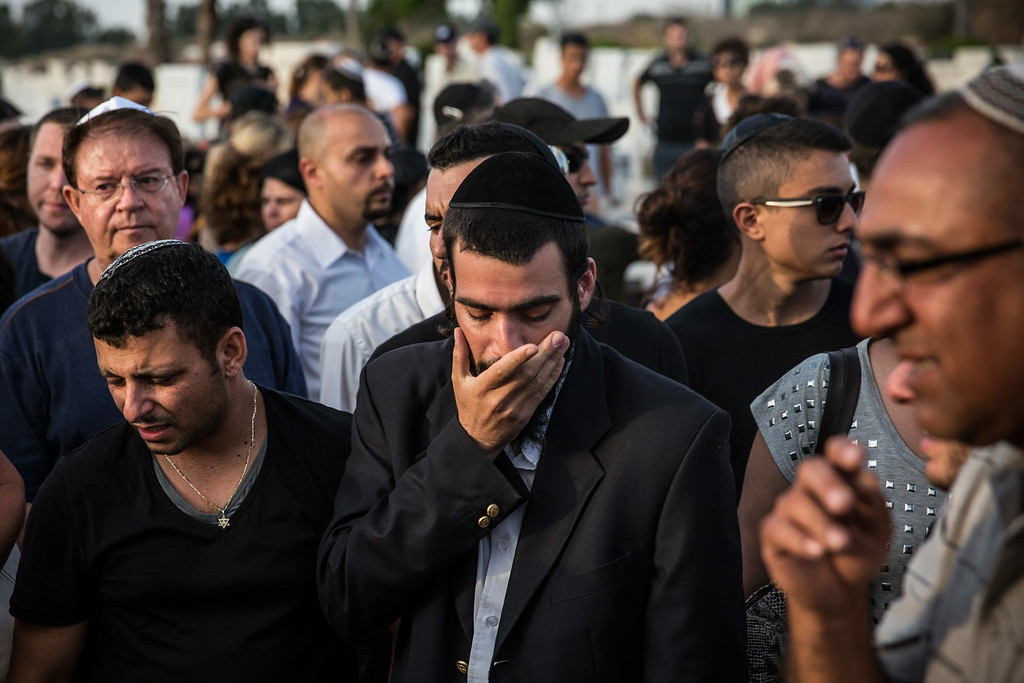 """. People mourn during the funeral of Dror Khenin at a cemetery on July 16, 2014 in Yahud Monoson, Israel. Yesterday Khenin was the first Israeli to be killed by a Hamas mortar as he offered food to Israeli soldiers working near the Erez border crossing between Israel and Gaza. As Operation \""""Decisive Edge\"""" enters its ninth day, over 200 Palestinians have been killed in Israeli missile strikes.  (Photo by Andrew Burton/Getty Images)"""