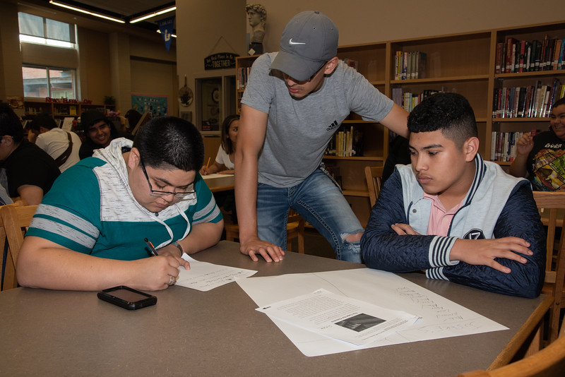 Justice Wallace (left) and Fernando Rocha with a West Oso High School student at the Spanish event at the library.