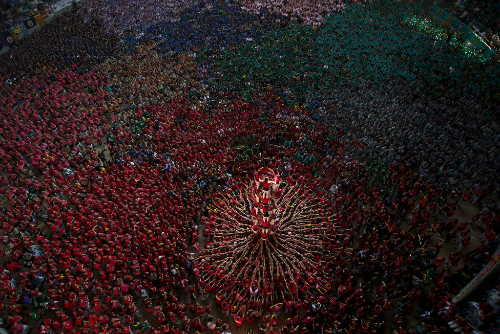 . Members of the Castellers Joves Xiquets de Valls try to complete their human tower during the 25th Human Tower Competition in Tarragona, Spain, on Sunday, Oct. 5, 2014. The tradition of building human towers, or castells, dates back to the 18th century and takes place during festivals in Catalonia, where colles, or teams, compete to build the tallest and most complicated towers. The structure of the castells varies depending on their complexity. A castell is considered completely successful when it is loaded and unloaded without falling apart. The highest castell in history was a 10 floor structure with 3 people in each floor. In 2010 castells were declared by UNESCO one of the Masterpieces of the Oral and Intangible Heritage of Humanity. (AP Photo/Emilio Morenatti, File)