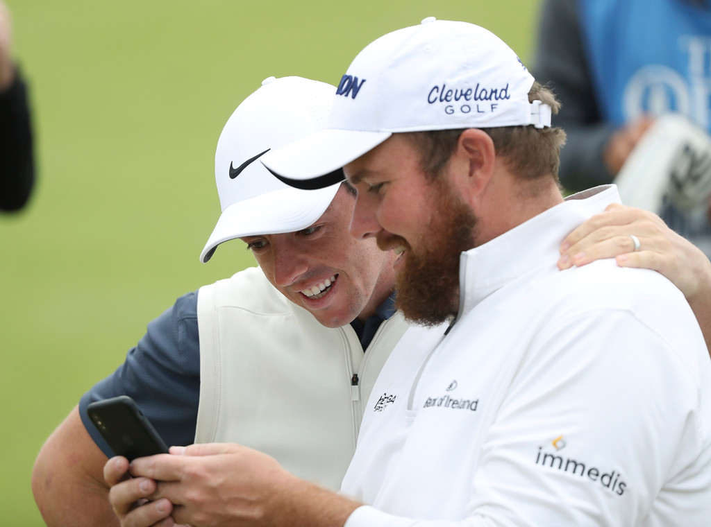 . Rory McIlroy of Northern Ireland, left, and Shane Lowry of Ireland look at a phone during a practice round ahead of the British Open Golf Championship in Carnoustie, Scotland, Wednesday July 18, 2018. (AP Photo/Peter Morrison)