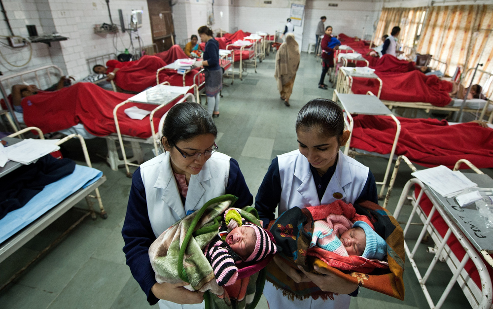 Description of . Indian nurses from Kasturba Gandhi hospital pose with two female babies born after midnight in conjunction with the date 12.12.12 in New Delhi on December 12, 2012. The once in a century date is being hailed as an auspicious day by astrologers, and many couples are getting married and expectant parents are flooding maternity homes, inundating doctors with requests to deliver their babies. PRAKASH SINGH/AFP/Getty Images