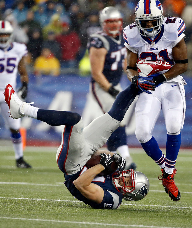 . New England Patriots wide receiver Julian Edelman (11) lands after making a catch in front of Buffalo Bills cornerback Leodis McKelvin (21) in the second quarter of an NFL football game, Sunday, Dec. 29, 2013, in Foxborough, Mass. (AP Photo/Elise Amendola)