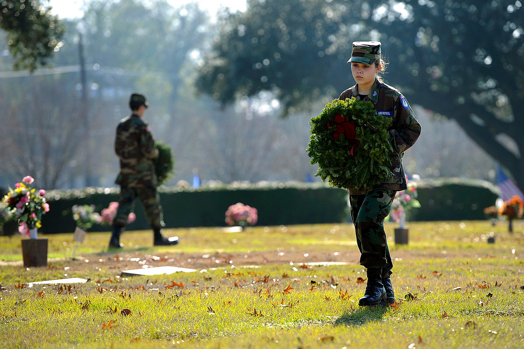 . Cadet Senior Airman Avery Griner, right, searches for a veteran\'s grave to place her tribute Saturday, Dec. 13, 2014, during Wreaths Across American Day at Sunset Memorial Park in Nacogdoches, Texas. The program started in 1992 at Arlington National Cemetery in Virginia and has spread to almost 550 locations nationally to honor deceased veterans and service members listed as missing in action during the holiday season. (AP Photo/The Daily Sentinel, Andrew D. Brosig)