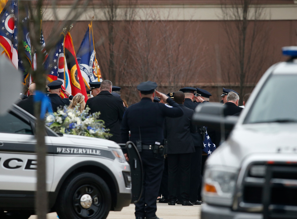 . A casket is taken into St. Paul the Apostle Catholic Church in Westerville, Ohio, before the start of funeral services for Westerville police officers Anthony Morelli and Eric Joering on Friday, Feb. 16, 2018. The two veteran officers were shot after entering a residence early Saturday afternoon. (AP Photo/Paul Vernon)