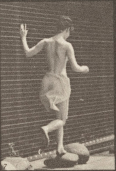 Semi-nude woman jumping from stone to stone across a brook