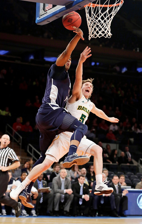 . Brigham Young\'s Brandon Davies (0) blocks a shot by Baylor\'s Brady Heslip (5) during the first half of an NIT semifinal basketball game, Tuesday, April 2, 2013, in New York. (AP Photo/Frank Franklin)