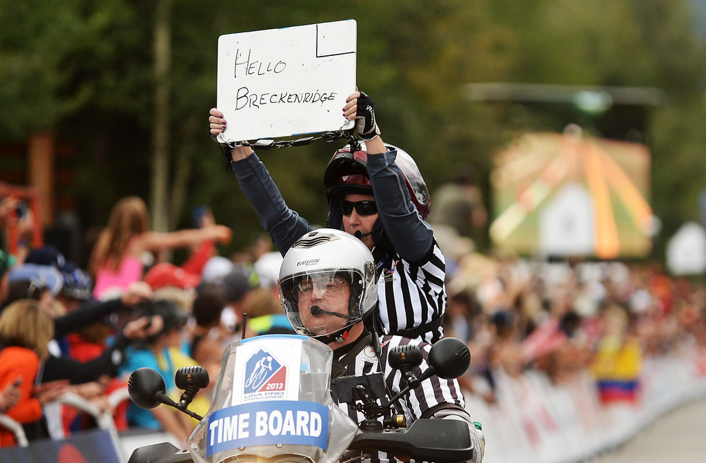 . An official holds up a sign to say hello to Breckenridge fans at the finish of Stage 2. (Photo By Hyoung Chang/The Denver Post)