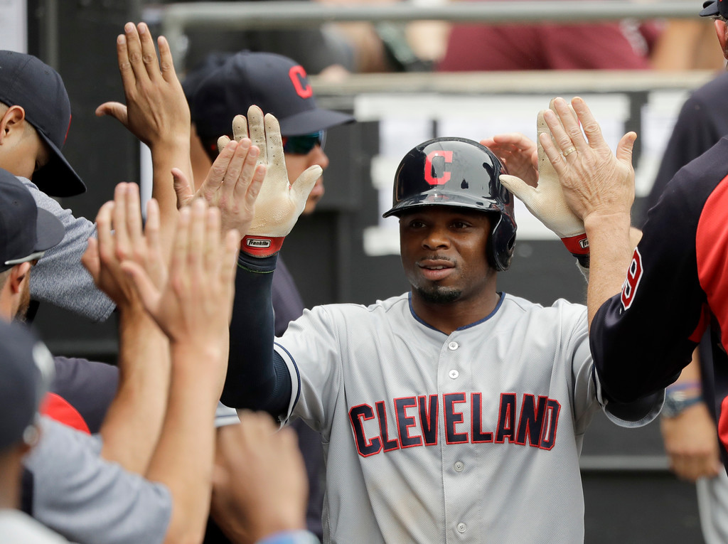 . Cleveland Indians\' Rajai Davis is greeted in the dugout after he scored on a bases loaded walk to Yan Gomes by Chicago White Sox starting pitcher Carlos Rodon during the third inning of a baseball game Thursday, June 14, 2018, in Chicago. (AP Photo/Charles Rex Arbogast)