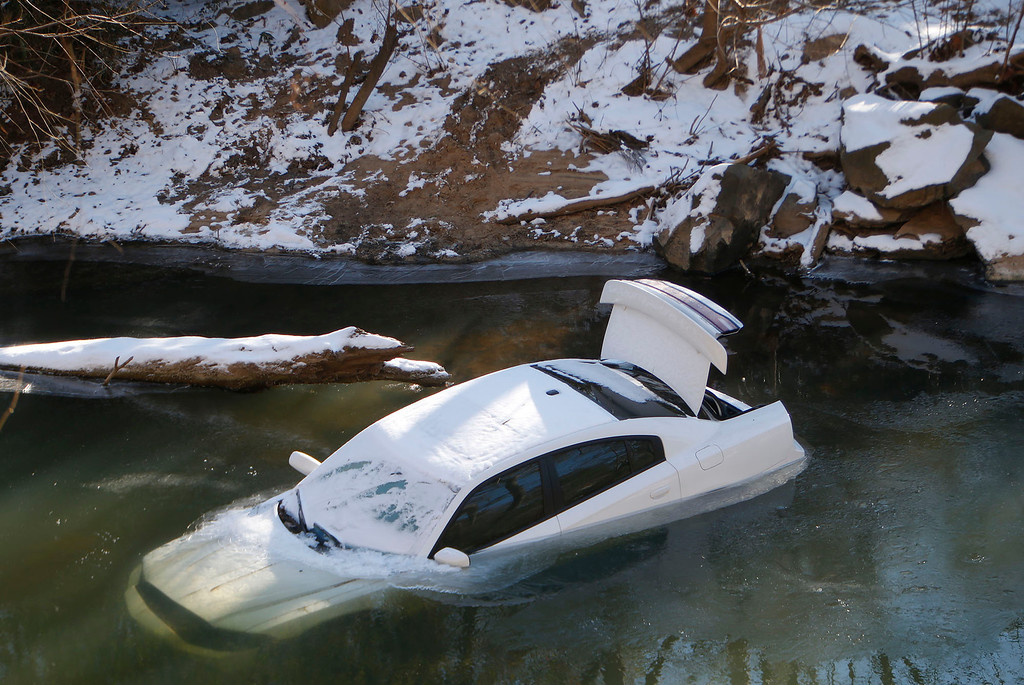 . A car lies half submerged in the Cahaba River Thursday Jan.30,  2014,. in Mountain Brook,  Ala. The driver was able to escape before the car slid into the river during Tuesday\'s snow storm and was not injured. (AP Photo/Hal Yeager)