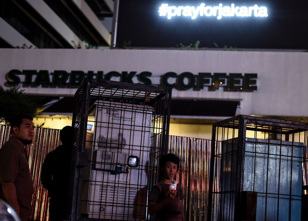 """. A young Indonesian boy (C) sips a drink outside the damaged Starbucks coffee shop after a series of explosions hit central Jakarta on January 14, 2016. A \""""Paris-style\"""" suicide strike on the Indonesian capital on January 14 confirmed Southeast Asian governments worst fears -- that citizens returning from fighting alongside the Islamic State group in the Middle East could launch attacks at home.     AFP PHOTO / MANAN  VATSYAYANA/AFP/Getty Images"""