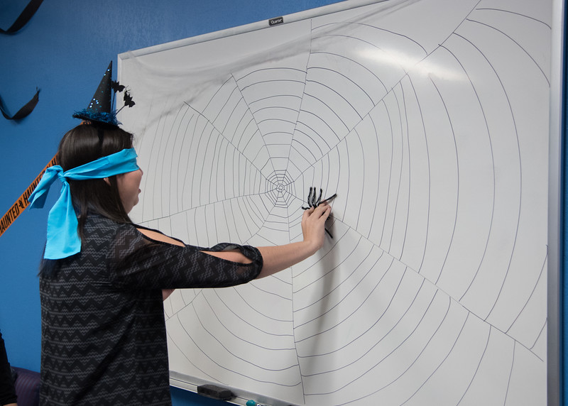 Student Andrea Rodriguez playing pin the spider on the web.